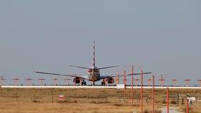 Vliegtuig op baan met baanlichten in voorgrond stock fotografie