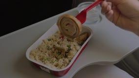 In vliegtuig op lijst is beschikbaar vaatwerk met een schotel van rijst en kip en een vrouw eet voedsel met een vork stock video