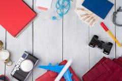 vliegtuig, paspoort, geld, camera, kompas, hoofdtelefoons, verrekijkers, jeans, blocnote, portefeuille stock foto's