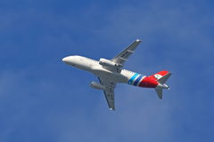 Vliegtuig superJet-100 rrj-95lr-100 op de achtergrond van blauwe hemel Stock Foto's