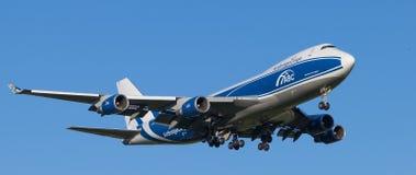 Vliegtuig uitnodigen die bij de luchthaven in de avond landen stock afbeelding