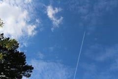 Vliegtuig ver weg in hemel met witte wolken en groene boom royalty-vrije stock fotografie