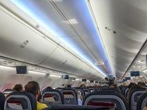Vliegtuigbinnenland die met gezette passagiers en perspectiefmening van start gaan van de zetels en de overheadkosten allen royalty-vrije stock afbeeldingen