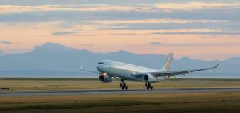Vliegtuigen die bij YVR bij schemer met bergen op de achtergrond landen royalty-vrije stock foto's