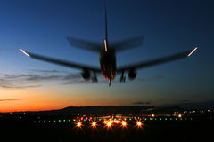 Vliegtuigen die bij Zonsondergang landen Stock Foto's