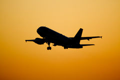Vliegtuigen die bij zonsondergang vliegen Stock Afbeeldingen