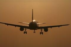 Vliegtuigen die in de zonsondergang landen Royalty-vrije Stock Foto's