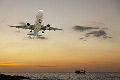 vliegtuigen die met toneelmening van mooie zonsondergang en overzees vliegen ove Stock Foto