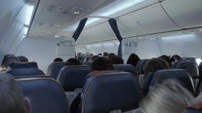 Vliegtuigencabine van uit de toeristenklasse in een modern passagiersvliegtuig met bewegende passagiers stock footage