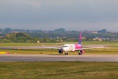 Vliegtuigenlijn Wizzair die op de luchthavenbaan taxi?en Stock Foto
