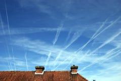 Vliegtuigensporen in de hemel boven een betegeld dak worden bespoten dat stock foto's