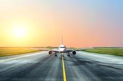 Vliegtuigentaxis na het landen in de avond bij zonsondergang bij de luchthaven Stock Afbeelding