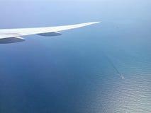 Vliegtuigenvleugel boven kalme overzees met nog water en schepen het verzegelen royalty-vrije stock afbeelding