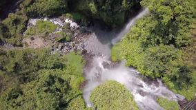 Vliegtuigmening van waterval in de wildernis, bij de bodem van het is er een meer met rotsachtige kust, rond is de dikke wilderni stock footage