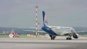 Vliegtuigparkeren dichtbij hangaar Grote witte passagiersjet op baan bij de luchthaven op een zonnige dag Binnen geparkeerd vlieg stock videobeelden