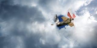 Vliegtuigstuk speelgoed in de bewolkte hemel stock foto