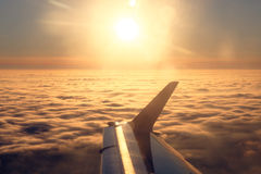 Vliegtuigvleugel en zon over de wolken Royalty-vrije Stock Afbeeldingen