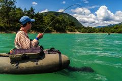 Vliegvisser bij bellyboat het vechten met grote forel, Slovenië Stock Foto