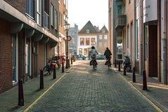Vlissingen holandie - Kwiecień 2015: Uliczny widok z nowożytnych czerwonych ceglanych domów i dwa dam jeździć na rowerze zdjęcia stock