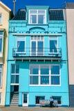 Vlissingen, Nederland - April 2015: Aturquoise overzees toevluchthuis met een mensenzitting op een bank voor het royalty-vrije stock foto