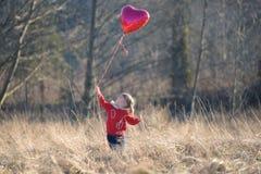 VLittle flicka som ser upp på denformade ballongen Royaltyfri Bild
