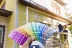 Välja en målarfärgfärg för husyttersida Arkivbild