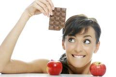 Välja mellan choklad och äpplet Arkivfoto