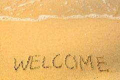 Välkomnande som är skriftlig i sand på strandtextur, mjuk våg av havet Resor Arkivfoton