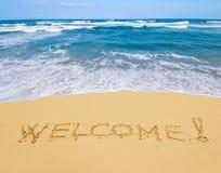 Välkomnande som skrivs i en sandig strand Arkivbild