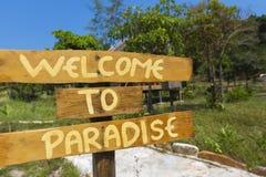 Välkomnande till paradistecknet med gröna träd och blå himmel i Cambod Arkivfoton