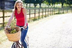 Vélo attrayant d'équitation de femme le long de ruelle de pays Images stock