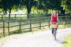 Vélo attrayant d'équitation de femme le long de ruelle de pays Images libres de droits