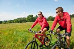 Vélo de montagne folâtre d'équitation de couples dans le pré Image stock