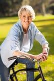 Vélo supérieur d'équitation de femme Images stock