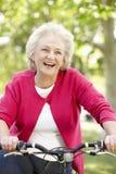 Vélo supérieur d'équitation de femme Photos stock