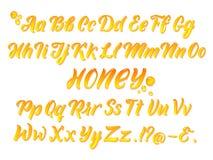 Vloeibaar honeyed Latijns alfabet met gouden plonsen Hand die gele brieven vectorreeks schrijven stock illustratie