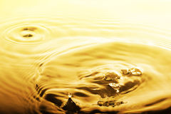 Vloeibare gouden daling en rimpeling royalty-vrije stock foto
