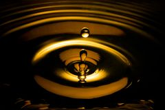 Vloeibare gouden daling en rimpeling in dark royalty-vrije stock afbeeldingen