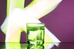 Vloeistof met ijs in een glas op een weerspiegelende oppervlakte op een roodachtige achtergrond royalty-vrije stock afbeelding