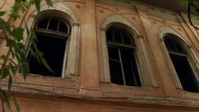 Vloek oud huis Een grote boom is dichtbij een vernietigd en verlaten huis gegroeid stock video