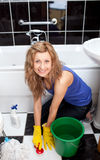 Vloer van de positieve jonge vrouwen de schoonmakende badkamers stock afbeelding