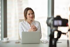 Vlog de enregistrement de jeune vlogger de femme d'affaires parlant à la caméra dedans photo stock