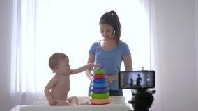 Vlog de Internet, muchacho feliz del niño con el vlogger de la madre jugado por los juguetes educativos mientras que registra el  almacen de metraje de vídeo