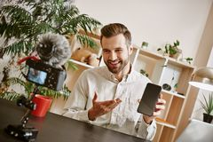 Vlog de technologie Nouvelle vidéo d'enregistrement masculin de blogger au sujet de smartphone moderne avec la caméra sur le prem photos libres de droits
