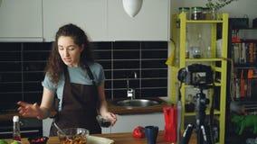 Vlog för mat för gladlynt attraktiv kvinnainspelning video om sund matlagning på digital kamera i köket hemma stock video