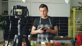 Vlog för mat för gladlynt attraktiv maninspelning video om sund matlagning på digital kamera i köket hemma stock video