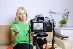 Vlog ou podcast video fêmea da gravação do blogger, fluindo em linha Câmera borrada no tripé na parte dianteira fotos de stock royalty free