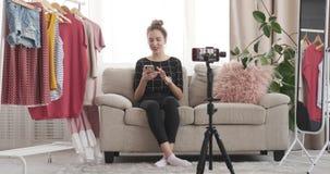 Vlogger da forma que grava o vídeo novo usando o telefone celular no boutique video estoque