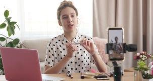 Vlogger de la belleza que presenta los cosméticos delante de la cámara móvil almacen de metraje de vídeo