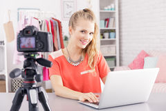 Vlogger editing her video. Female vlogger sitting beside desk with laptop, editing her video royalty free stock photo